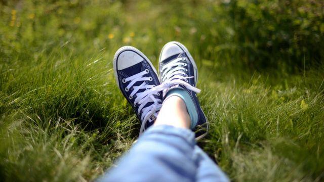 Pernas esticadas na grama