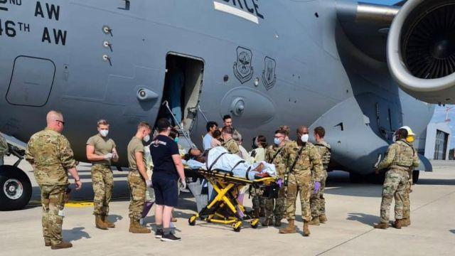 Las fuerzas estadounidenses llevan a una madre y un bebé recién nacido para recibir atención médica después de que las mujeres dieron a luz en un vuelo de evacuación desde Afganistán.