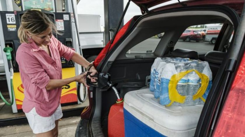 Woman fills up a gallon of gasoline