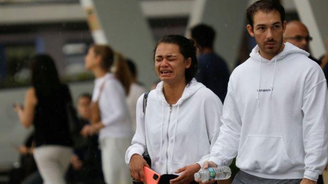 Mujer llora a las puertas del centro de reunificación familiar tras el colapso de un edificio en Surfside