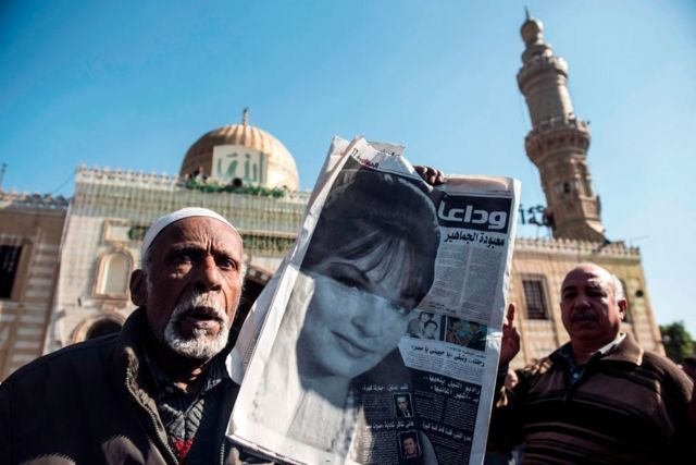 """Two Egyptian men, one of whom carried a newspaper with a picture of Shadia and a headline saying """" Goodbye, the idol of the masses."""
