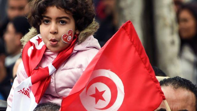 طفلة تتلفع بـ علم تونس