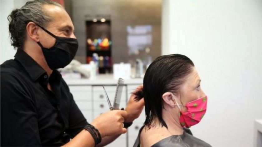 Hairdresser attends client, both wear protective masks against covid-19
