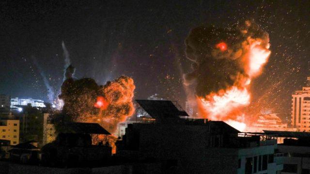 تضيء الانفجارات سماء الليل فوق المباني في مدينة غزة مع قصف القوات الإسرائيلية للقطاع، 18 مايو/أيار 2021