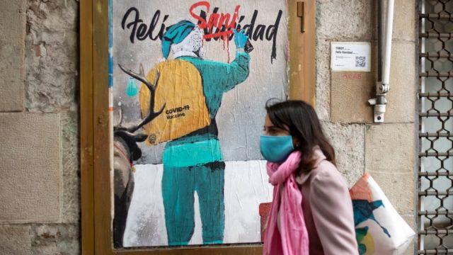 一名妇女走过意大利街头艺术家TvBoy的一件新作品,该作品描绘了圣诞老人在麻袋中携带Covid-19疫苗。