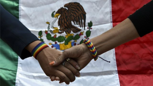 Mãos entrelaçadas com a bandeira mexicana