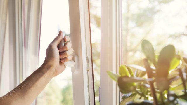 Um homem abrindo uma janela