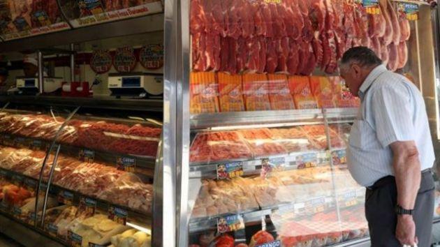 Homem compra carne em açougue em Santo André, São Paulo