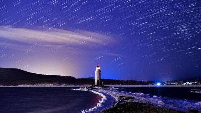 Rastros de meteoros sobre o mar, no meio do qual há um farol