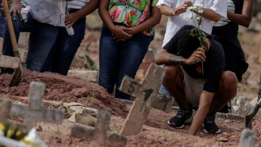 코로나19로 가족을 잃은 사람들이 꽃을 들고 있다
