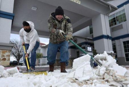 Duas pessoas retiram neve da entrada de casas no Texas