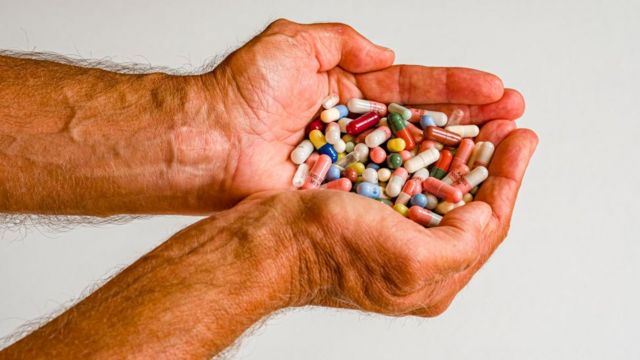 A man holding two handfuls of pills