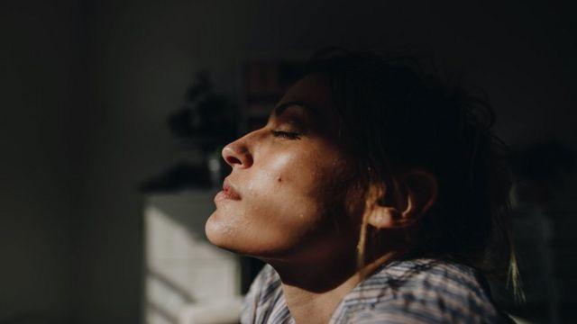 امرأة في الداخل وأشعة الشمس تنعكس على وجهها