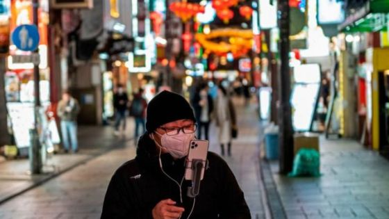 一名男子带着电话走过横滨的唐人街