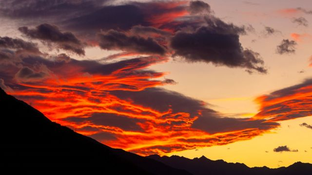 Bright red and orange clouds, over some dark mountains
