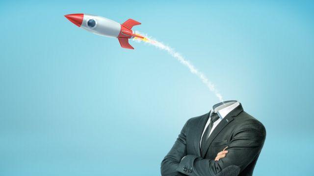 Cohete despegando de la cabeza de un hombre.