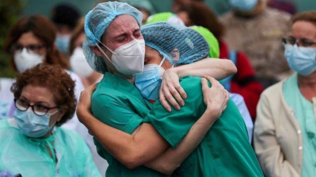 Profissionais de saúde se abraçam após a morte de um colega na Espanha
