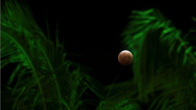 Uma superlua, a maior e mais brilhante lua cheia do ano, coincide com um eclipse lunar total, fazendo com que a lua pareça vermelha no céu de Honolulu, Havaí, nos EUA