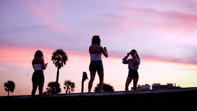 Jóvenes toman fotos en el atarrdecer