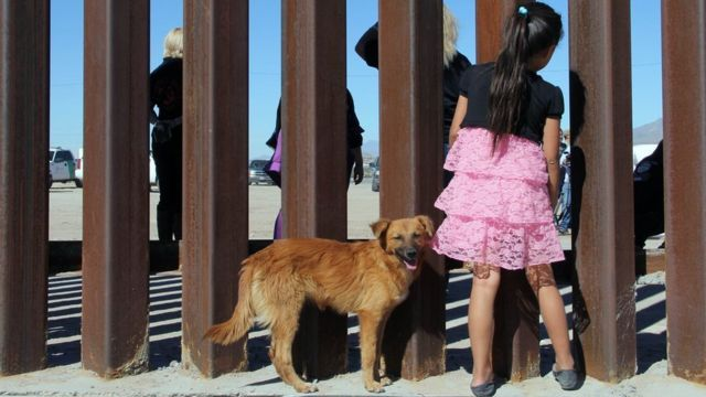 A girl in Mexico looks through the fence to the United States