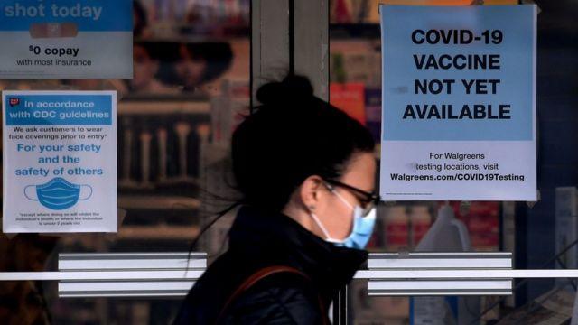 Una mujer pasa junto a un letrero que informa que no hay vacunas disponibles aún en Arlington, Virginia.