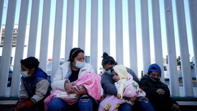 Ciudadanos de El Salvador y Honduras que buscan asilo en Estados Unidos se sientan frente al cruce fronterizo de El Chaparral el 19 de febrero de 2021 en Tijuana, México.