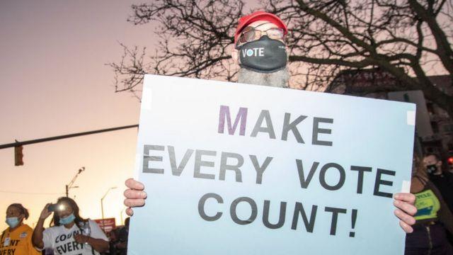 """Un manifestante en Michigan sostiene un cartel que dice """"Hagan que cada voto cuente"""""""