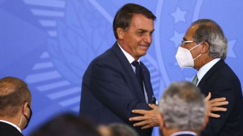 Jair Bolsonaro and Paulo Guedes shake hands