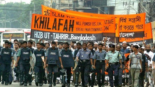 """Hizb-ut Tahrir üyelerinin Bangladeş'teki bir gösteride taşıdığı pankart: """"Hilafet Savaş Suçlusu ABD, İngiltere ve İsrail'i Cezalandıracak""""."""