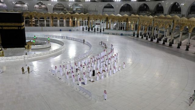 In this file photo taken on April 27, 2020, worshippers perform Isha prayer while keeping distance between them next to the Kaaba in Mecca's Grand Mosque