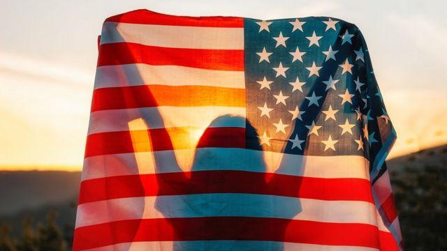La sombra de una mujer con la bandera de Estados Unidos.