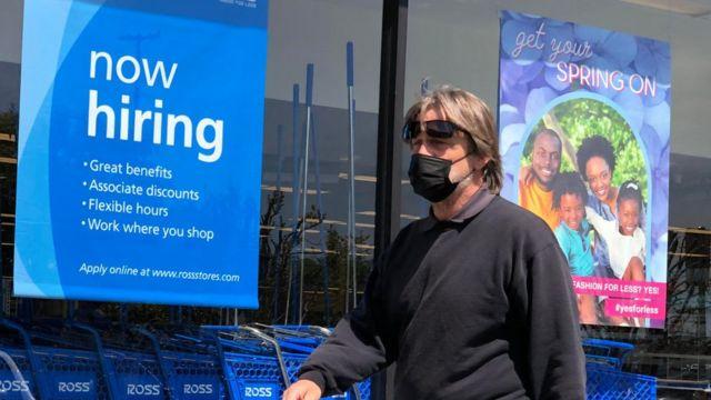 Un comercio con un cartel que ofrece empleo en California.