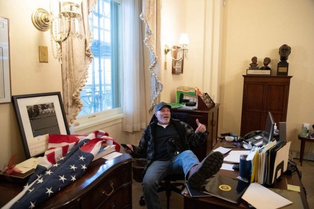 Richard Barnett, sits with one boot disrespectfully on a desk that is at the very centre of power in Congress.