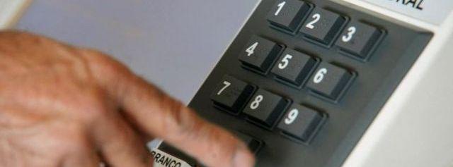 Homem digita em urna eletrônica