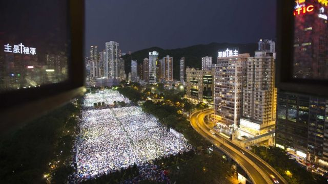 """Tens of thousands of people participate in a candlelight vigil at Hong Kong""""s Victoria Park June 4, 2013, to mark the 24th anniversary of the military crackdown of the pro-democracy movement at Beijing""""s Tiananmen Square in 1989."""