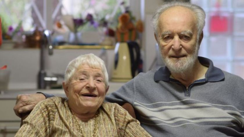 An elderly couple embraces and smiles