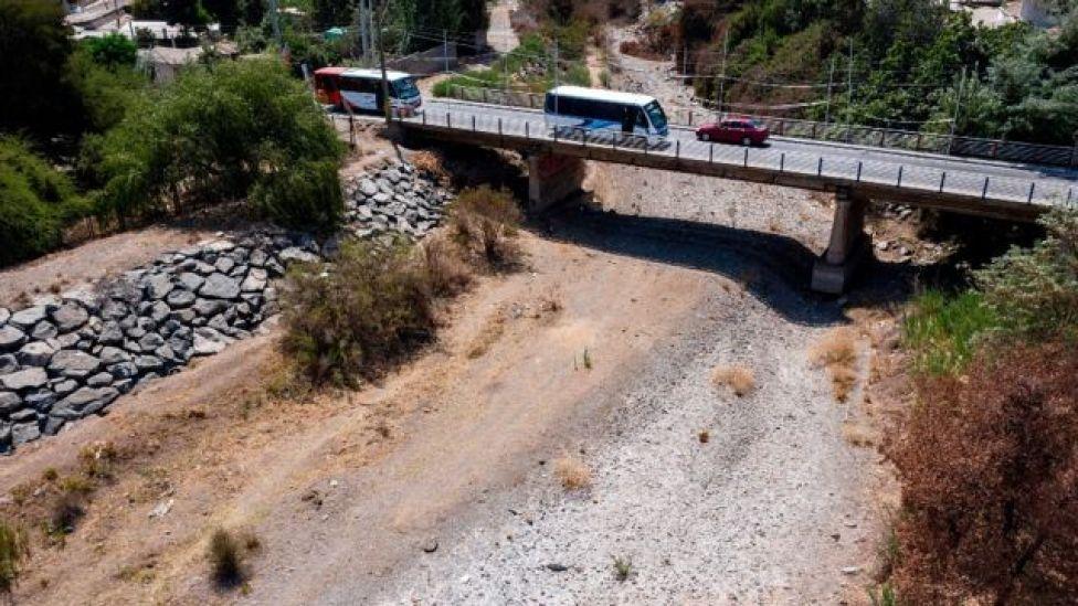 Vehículos cruzando un puente sobre el río Melón seco en Chile