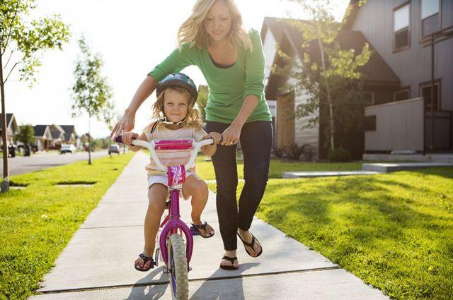 Garotinha anda de bicicleta com a ajuda de uma mulher