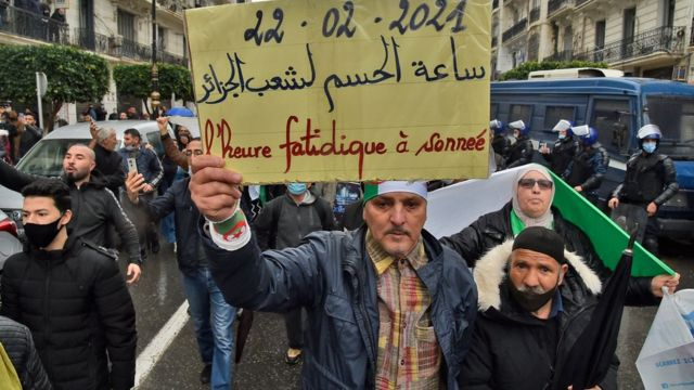 """Demonstrators raise a banner written on it """"Decisive hour for the people of Algeria"""""""