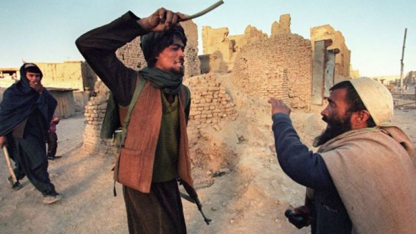 A Taliban militant punishing another man in Afghanistan