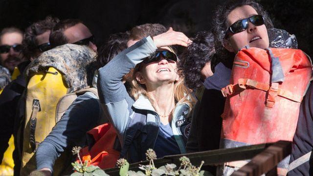 Voluntarios con gafas oscuras a la salida de la cueva de Lombrives