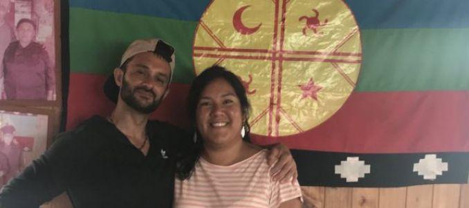 María y Daniel frente a una bandera mapuche.