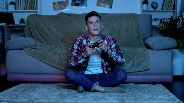 Jovem segura controle de videogame e olha para televisão