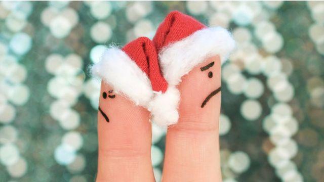 Dedos con rostros pintados y sombreros de Papá Noel de espaldas uno al otro