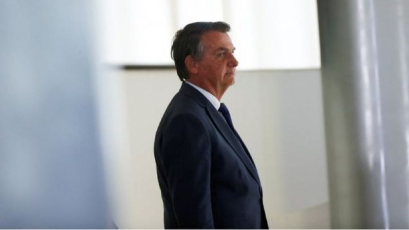 Bolsonaro standing in the hallway, with a restrained smile