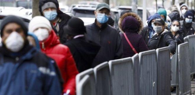 Dezenas de pessoas enfileiradas em área externa, com máscaras e roupas de frio