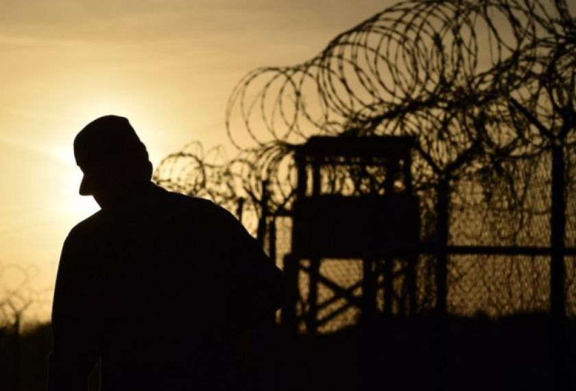 Silhouette of soldier and prison fence in photo taken against the sun.