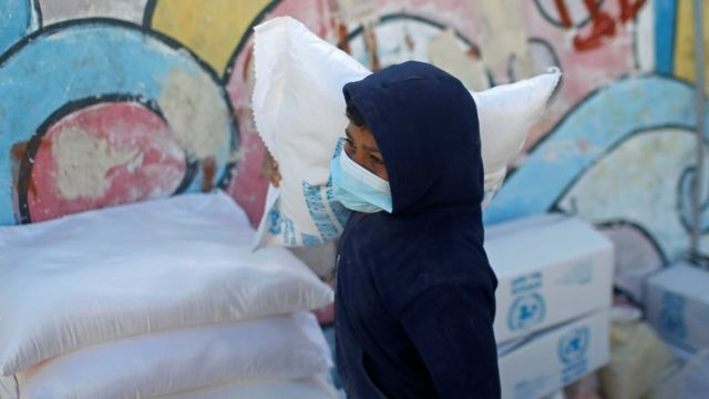 A Palestinian child carries a bag of flour in aid in Gaza
