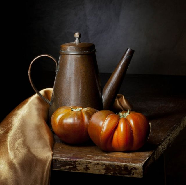 An old copper kettle on a table with large tomatoes