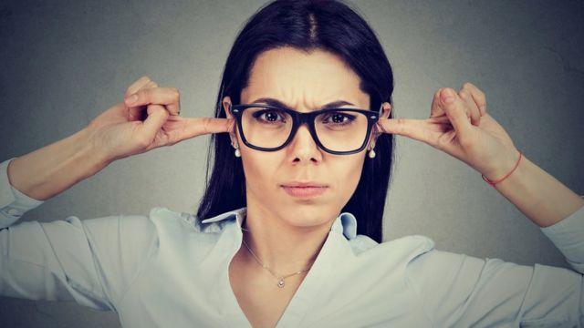 Une femme se bouche les oreilles